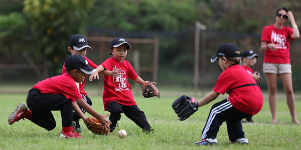 image of youth baseball players running to get ball